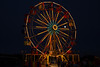 A full  moon between the spokes of the ferris wheel at the Pioneer Days carnival in Guymon, Oklahoma.<br /> Photo © Cindy Clark