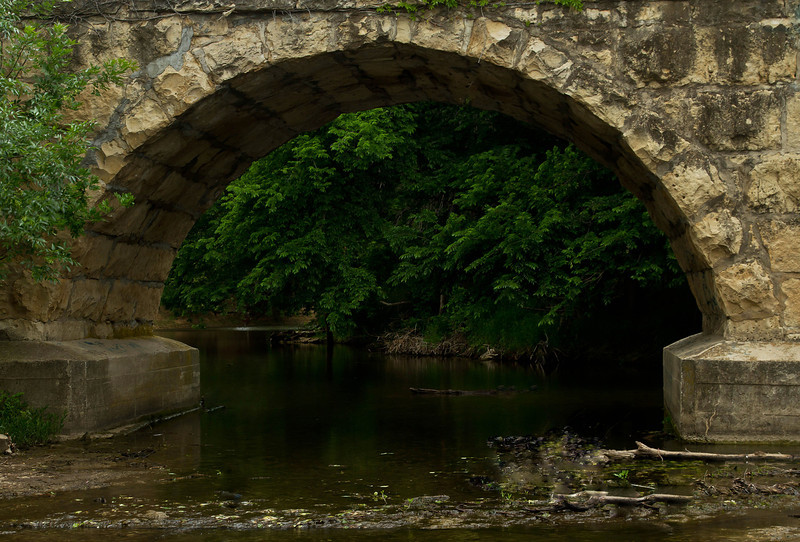 The lovely curve of a stone bridge frames a river scene in Kansas.<br /> Photo © Cindy Clark