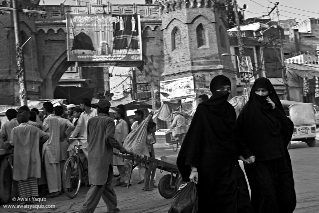 Belief System: Two ladies covered in burka passing by crowd of men busy in some other stuff. Shot in Multan,  also known as city of Saints.