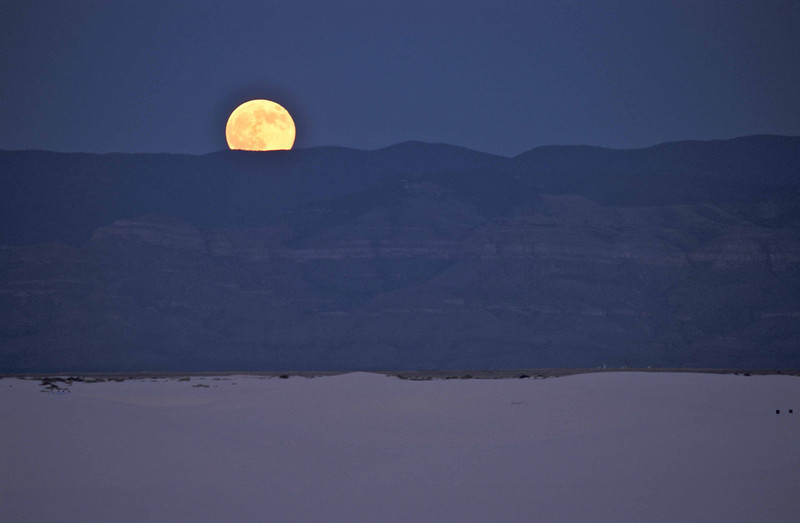The full moon emerges over the Sacremento Mountains at White Sands.<br /> Photo © Carl Clark