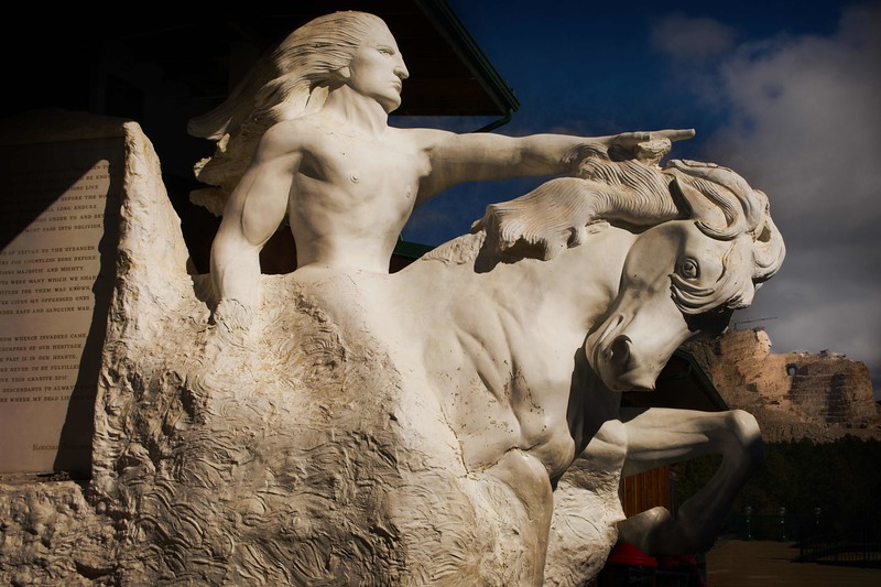 A model of the Crazy Horse Memorial with the actual rock carving in the background. This was begun in 1948.<br /> Photo © Cindy Clark
