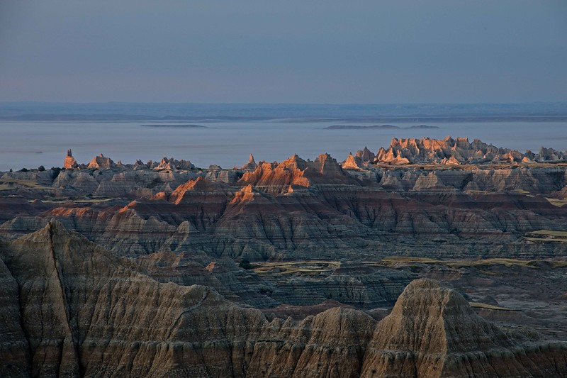 Fog in the distance sets off the morning forms in the South Dakota Badlands.<br /> Photo © Carl Clark