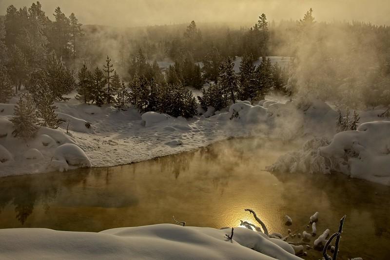 Morning sunlight streams through the geyser fog in Yellowstone.<br /> Photo © Carl Clark