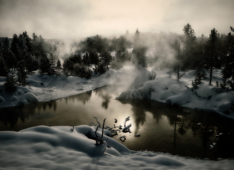 Sun filtering through the steam from a geothermal pool at Yellowstone.<br /> Photo © Cindy Clark