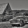 Old Chevy truck parked in front of a shack. Bakersville - a seed store and fantasy town near Mansfield, Missouri. Black and white high dynamic range version.