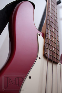 Four Strings to a Curve - Semi-abstract photo of a red Fender Jazz bass guitar.