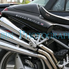 Custom triple pipes on a Triumph motorcycle.