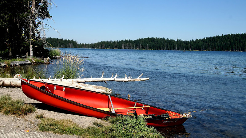 A lovely red canoe against the blues of the sky and Diamond Lake in central Oregon.