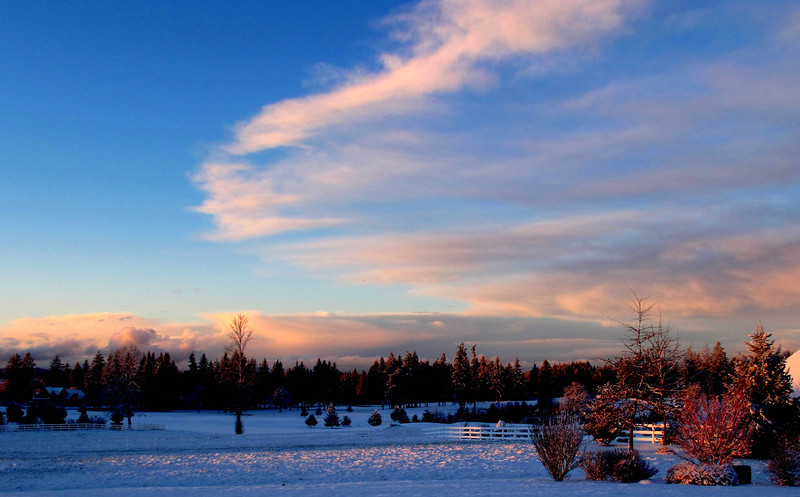 After a late February snow storm, the sky cleared and the sun returned.. Playing pink and orange on the clouds.