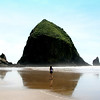 A solitary girl walks to Haystack Rock on a beautiful summer's day in Cannon Beach Oregon