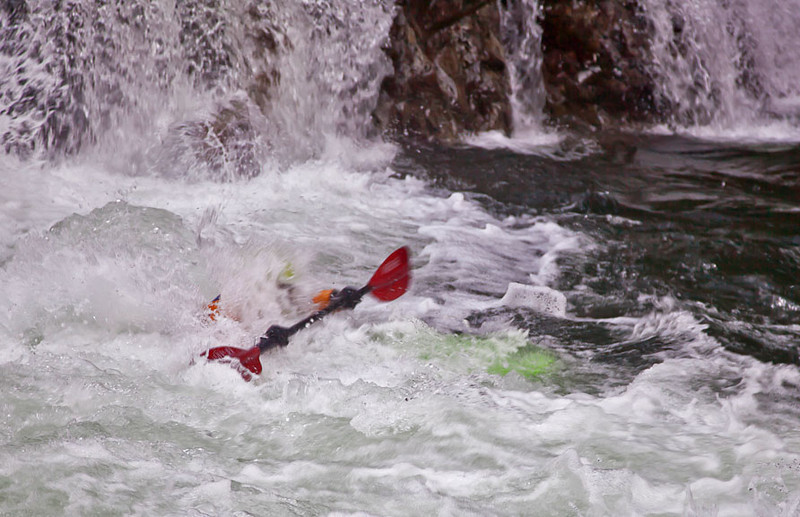 As a kayaker comes over the falls they find themselves under the water in this shot.