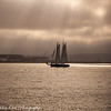 As the sun battles the low clouds in San Diego, a sailing boat catches the last rays poking through the clouds with a backdrop of the Coronado Navy Base and Point Loma.