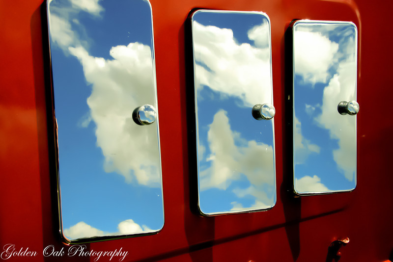 The hood of this 1928 Ford shows the dreamy reflection of the sky in the chromed hood vents..Love the deep red and the puffy clouds!