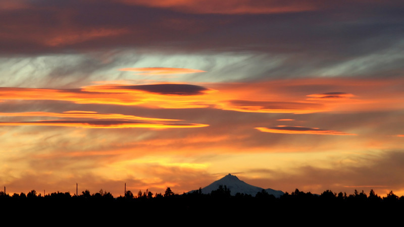 Last weekend the sunset near Redmond Oregon was spectacular...this was taken around 9:30 PM...Mt Hood is in the distance.this was all natural...taken while driving as we were Very late for dinner...Mt Hood had 52 FEET of snow this past year...still skiing up there!