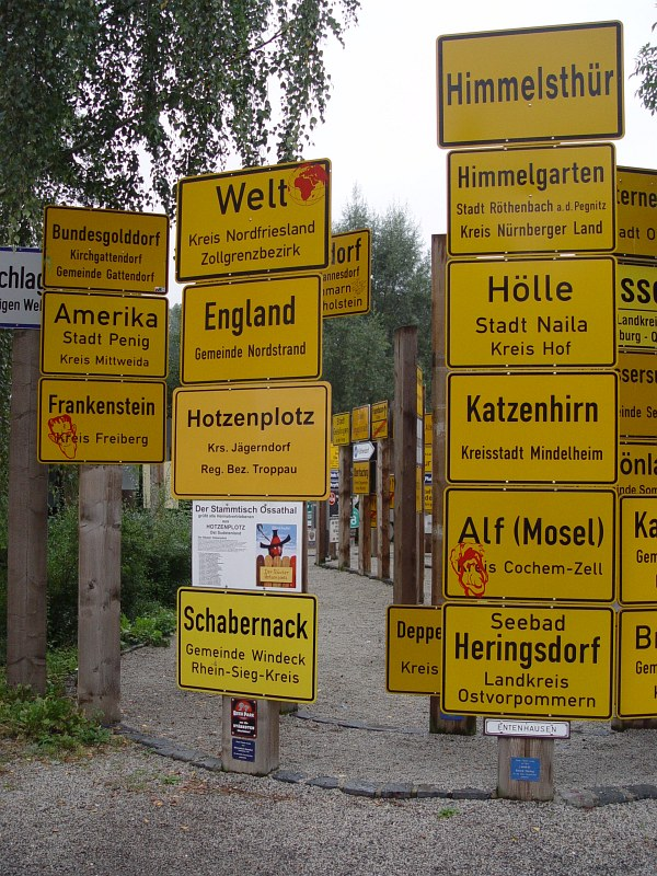 2005-09-12_06297 die Ortseingangsschilder sprechen für sich selbst the place name signs speak for themselves, at least in German - from top to bottom+left to right: 1.row 'Federal Gold Town', 'America', 'Frankenstein', 2. row 'World', 'England', 'Hotzenplotz' (name), 'Prank', 3. row 'Heaven's Door', 'Heaven's Garden', 'Hell', 'Cat Brain', 'Alf' (you know - the hairy guy on TV), 'Herring Town'