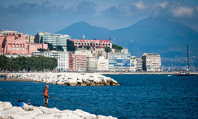 A rod and line fisherman in the harbour at Naples with Mt Vesuvious in the background