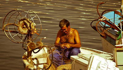 A fisherman fixing his nets in the harbour, Naples, Italy