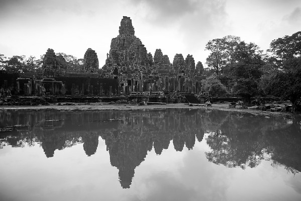 "Bayon is at the heart of Angkor Thom (which translates literally as ""Great City""). The temple itself has no walls or moat because those of Angkor Thom provides all of the protection it needs.  Built later than Angkor Wat (during King Jayavarman VII's reign) as a buddhist temple, it features a very different style of architecture than what we have previously seen."