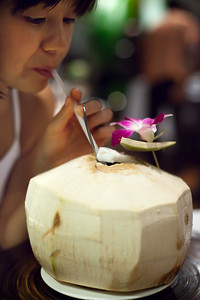 Valerie sips juice from another massive coconut