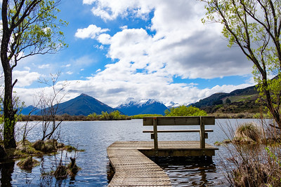 Bench at the end of a boardwalk by a lake in South Island, New Zealand