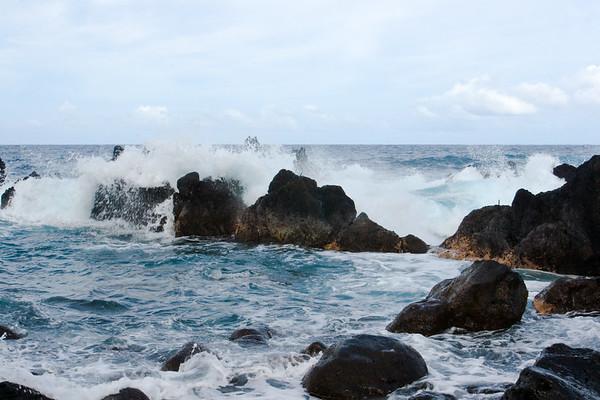 Waves crash against the lava rock