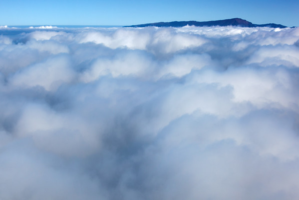 Haleakala is barely visible above the clouds before we drop into them