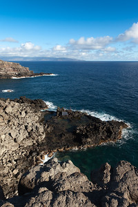 As I look over the edge of the cliff, I see men fishing on a lava shelf below