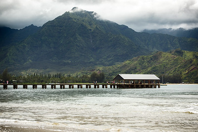 Another waterfall descends within view of Hanalei Pier