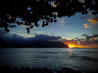 Specular highlights fade upon the waves and the sun dips behind Kauai