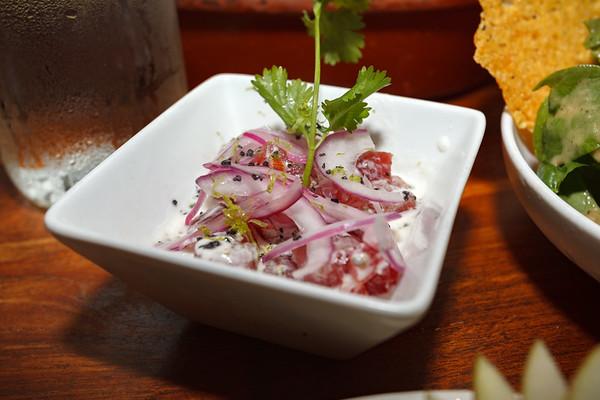 Ahi Poké with slivered red onions, cilantro, lime, and leché de tigre...like ceviche