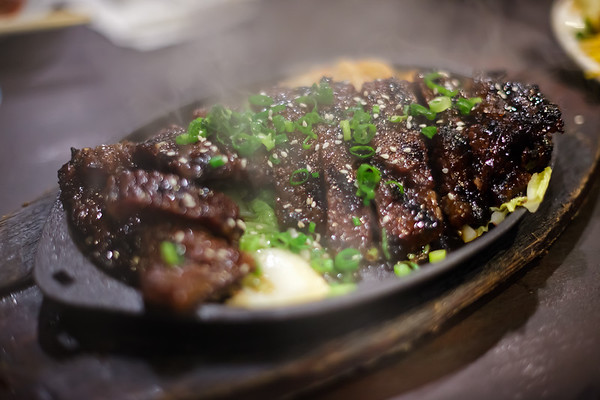 Concerned we aren't getting enough to eat, Phylo and Michele order a round of Sizzling Boneless Kalbi