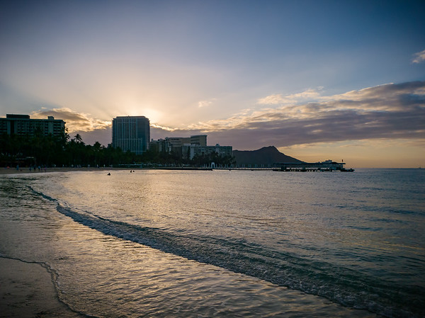 From Kahanamoku Beach, the sun will soon emerge from the clouds but behind Trump International Hotel Waikiki