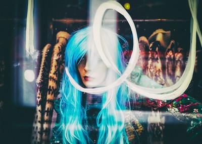 A retail shop mannequin seen through a painted window.