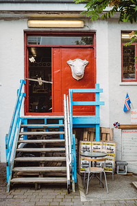 Found this scene of a cow head sculpture hanging on a red wall with a blue stairway railing in Reyjkavik.