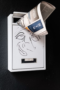 A newspaper sticking out of a mailbox with a character's face drawn on it.