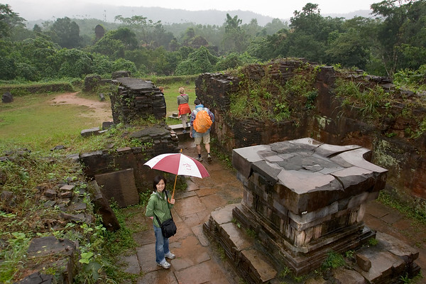 Valerie stands in the rain near an ancient device that does something with water