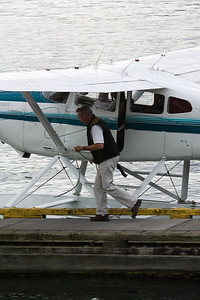 The pilot hops out to tie the plane to the dock