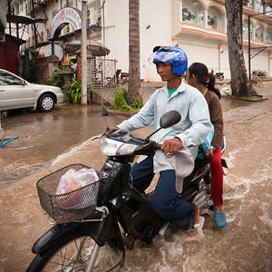 A father and daughter ride a scooter on the flooded streets of Siem Reap