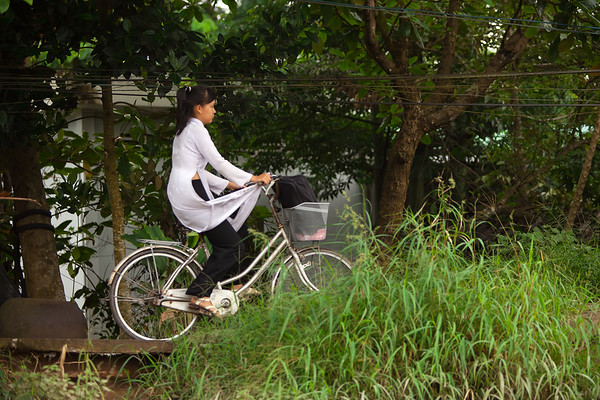 A girl wearing an ao dai rides her bike home from school along a path overlooking the canal