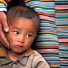 A young boy is comforted by his mother.<br /> Boulder has a sister city relationship with Llasa, Tibet. A delegation from Boulder and around the world visited Tibet in 1999 to help locals learn about solar energy and how they could use it.<br /> Cliff Grassmick