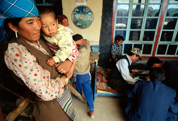A mother and son watch the delegation install solar electricity in their home.<br /> Boulder has a sister city relationship with Llasa, Tibet. A delegation from Boulder and around the world visited Tibet in 1999 to help locals learn about solar energy and how they could use it.<br /> Cliff Grassmick