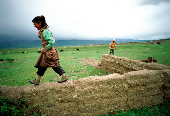 Children walk along the the yak dung and mud walls in rural Tibet.<br /> Boulder has a sister city relationship with Llasa, Tibet. A delegation from Boulder and around the world visited Tibet in 1999 to help locals learn about solar energy and how they could use it.<br /> Cliff Grassmick