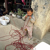 A boy chews on the solar wiring, thinking it was candy in rural Tibet.<br /> Boulder has a sister city relationship with Llasa, Tibet. A delegation from Boulder and around the world visited Tibet in 1999 to help locals learn about solar energy and how they could use it.<br /> Cliff Grassmick