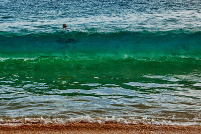 Big Beach, Makena, Maui - There is just one breaker. Almost on shore. You can see the bottom of the ocean very deep in to the water through the breaker wall because of it's clarity. You can see the man's body siting on a boogie board through the water.