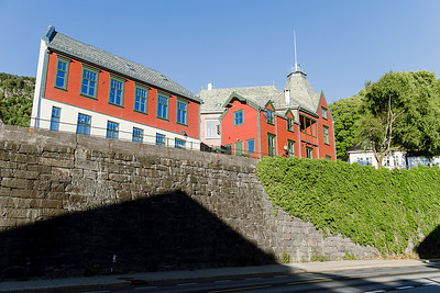 A reddish building on Johan Mohrs gate 5036 Bergen, Norway, seen from the road below,  Fv585.