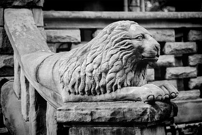 A content-looking, decorative concrete lion atop a step-railing in Pittsburg.
