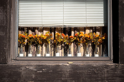Glass bottles filled with white sand and yellow-orange flowers sit on a sunny window sill with blinds above them in Pittsburg.
