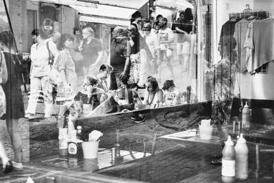 Window reflections of a bustling scene in Gamla Stan.