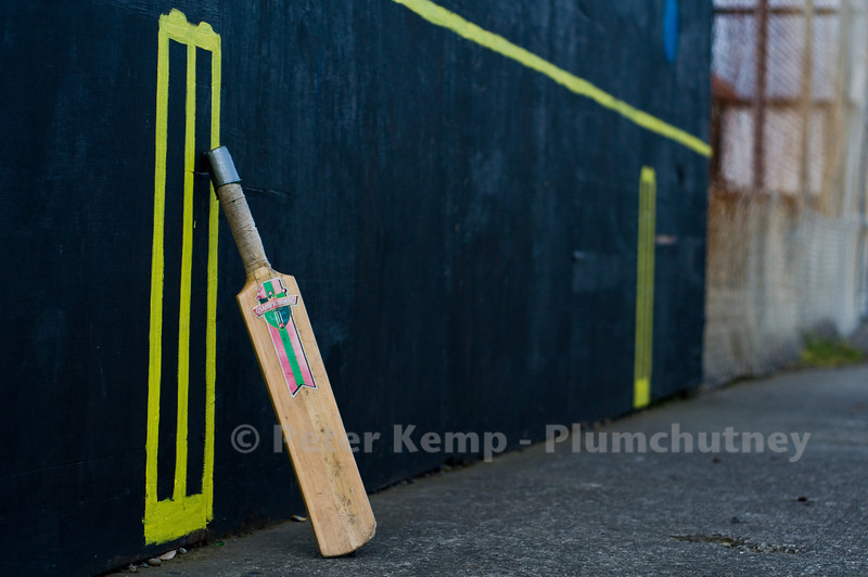 Cricket bat leaning against painted stumps in playground