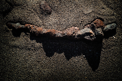 A rusty metal rod encrusted with rocks and sand casts a long, mountainous shadow on Double Bluff Beach.